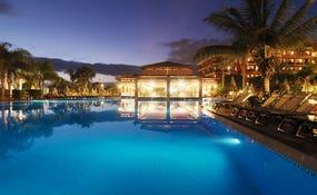 Vista nocturna del hotel y la piscina