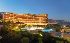 General view of the hotel and swimming pools at dusk
