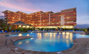 General view of the hotel and swimming pool at dusk